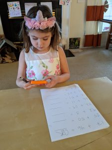 Young girl completing a math worksheet