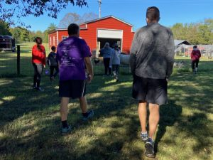Participants walking by red barn during event.