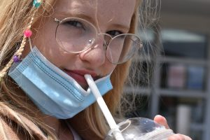 Teenage girl in face mask drinking a coffee