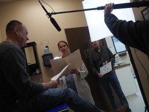 Rehearsal hospital scene show Leslie Price (Doctor), Shawn Hawthorne on table, Todd Gorden holding clapper, Izzy Gorden holding boom mic and Seth Vance taking photo. Taken at Fullwood Animal Hospital