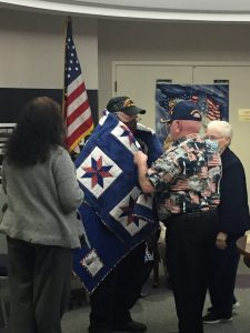 Mr. Davis receives his quilt with Mrs. Kelly Coble, and Mr. & Mrs. Mayhill.