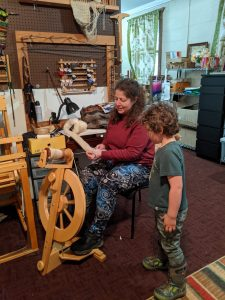 Woman demonstrates hand spinning to child