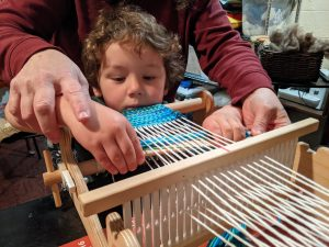 Woman helping a child weave on a loom