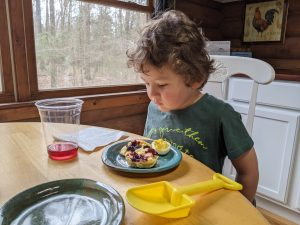 Child eating a scone topped with elderberry jam and drinking herbal tea
