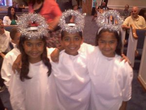 Triplets dressed as angels for a performance