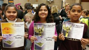 Triplets proudly displaying academic awards