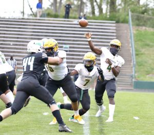Indy's quarterback Arnold Taylor passes while being protected by Messiah Lopez and Amari Hakem (7).  Photo by Ron Morris
