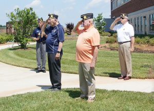 Legionnaires from Post 555 saluting during the playing of taps.