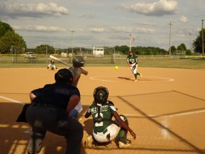 Taylor Houseton tossing a strike, Mikenna Williams behind the dish.