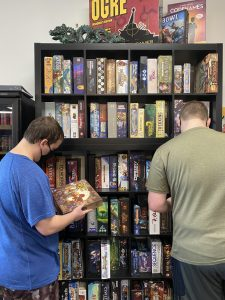 Patrons peruse the shelves at Your Local Game Store for something to rent or purchase.