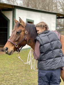 Young woman hugging horse