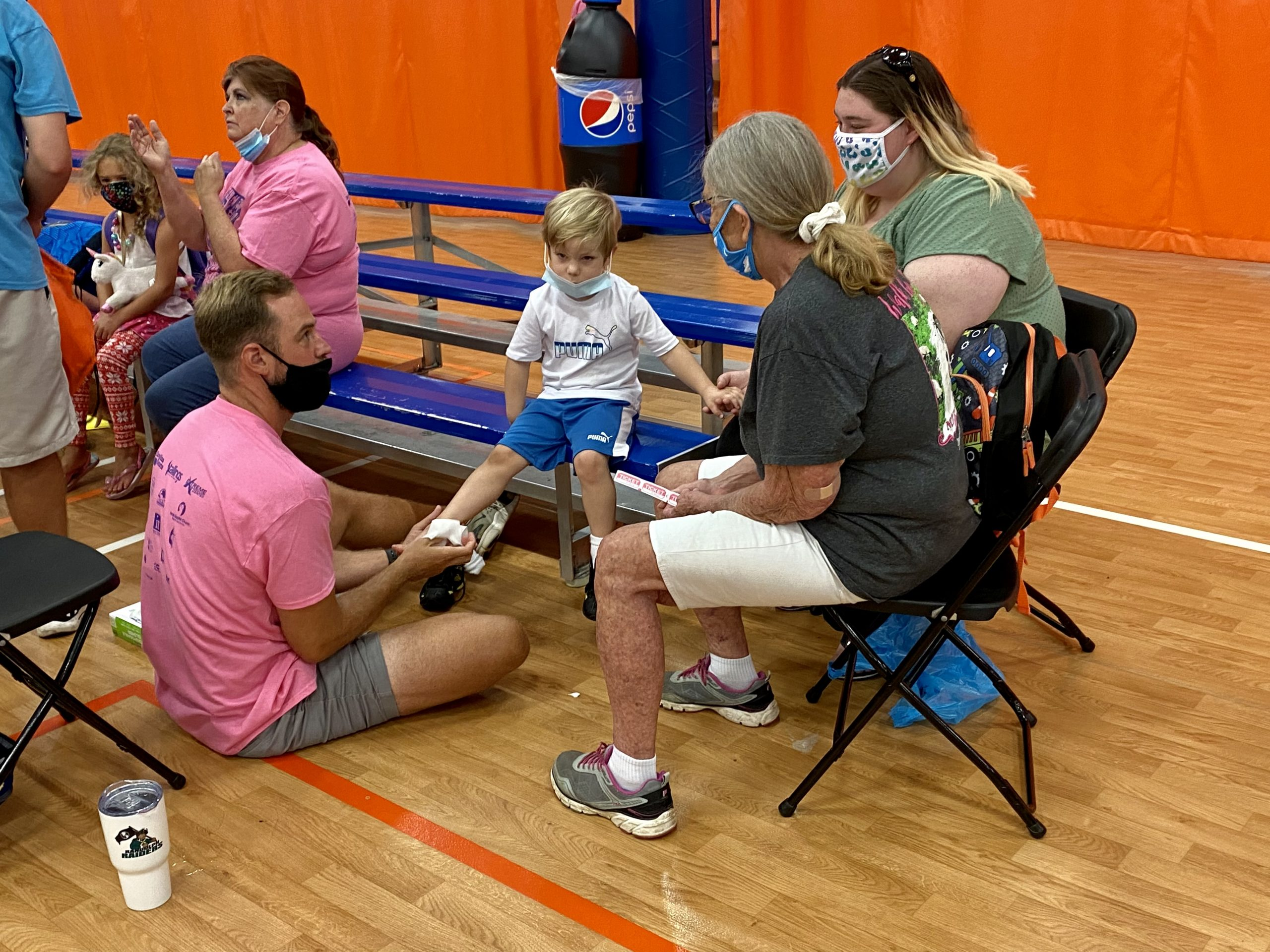 A volunteer cleans a child's foot before sizing him for sneakers on Aug 14, 2021.
