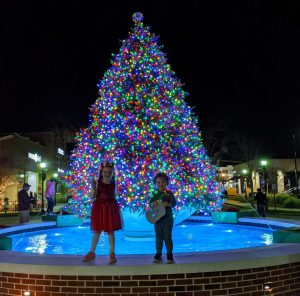 children standing in front of lit Christmas tree