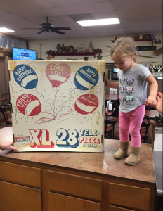 Toddler standing next to 28 inch pizza