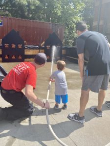 Maddox, 2, is putting out the fire with some support from the Waxhaw Fire Department.